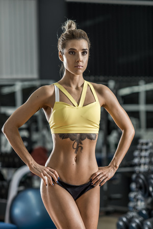 young fitness woman in gym, vertical photo