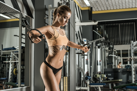 gym workout: young fitness woman execute exercise with exercise-machine Cable Crossover in gym, horizontal photo