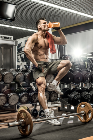 food supply: guy bodybuilder tired sit in gym and drink sportive nutrition - protein of shaker , vertical photo