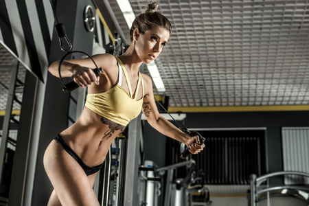 crossover: young fitness woman execute exercise with exercise-machine Cable Crossover in gym, horizontal photo