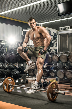 musculation: guy bodybuilder tired sit in gym, vertical photo