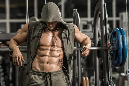 man bodybuilder moe fitnessruimte en muziek luisteren met een hoofdtelefoon