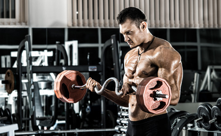 physical training: guy bodybuilder , execute exercise with weight in gym, horizontal photo