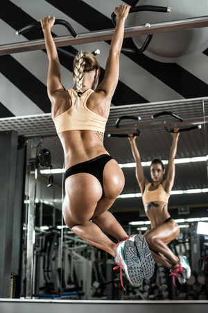 tough woman: young fitness woman execute exercise on prelum abdominale, on horizontal bar in gym, vertical photo Stock Photo