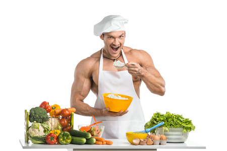 musculation: Man bodybuilder in white toque blanche and cook protective apron, eating cottage cheese , on whie background, isolated