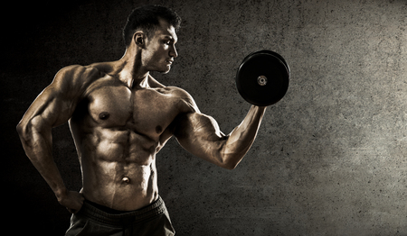 man at work: very power athletic guy , execute exercise with dumbbells, on concrete slab background Stock Photo