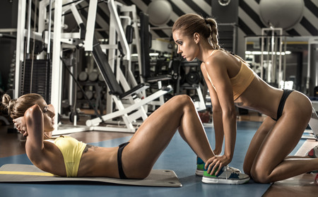 musculation: two young fitness woman, execute exercise on prelum abdominale in gym, horizontal photo Stock Photo