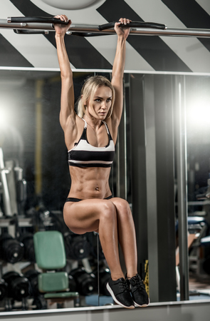 musculation: young fitness woman, execute exercise on horizontal bar in gym, vertical photo