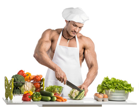 musculation: Man bodybuilder in white toque blanche and cook protective apron, concoction vegetables and fruit , on whie background, isolated