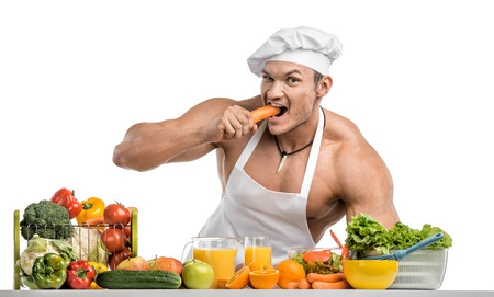 Man bodybuilder in white toque blanche and cook protective apron, gnaw carrot , on whie background, isolated Stock Photo