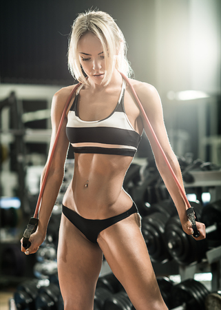 pulling beautiful: young fitness woman execute exercise with expander in gym, vertical photo