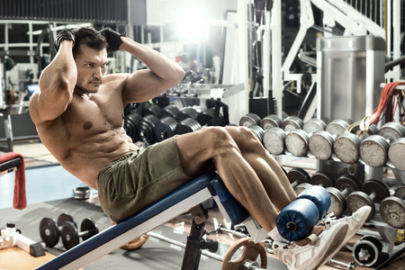 musculation: guy bodybuilder , execute exercise on prelum abdominale on bench in gym, horizontal photo