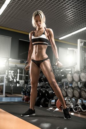 tough girl: young fitness woman execute exercise with expander in gym, vertical photo