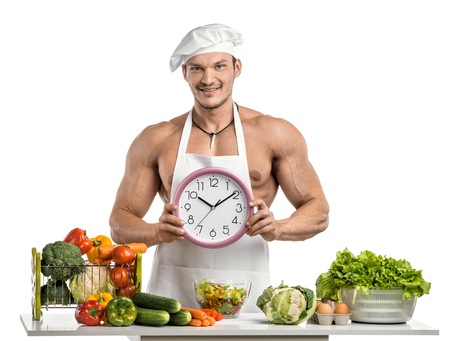 toque blanche: Man bodybuilder in white toque blanche and cook protective apron, hold on hands clock , on whie background, isolated