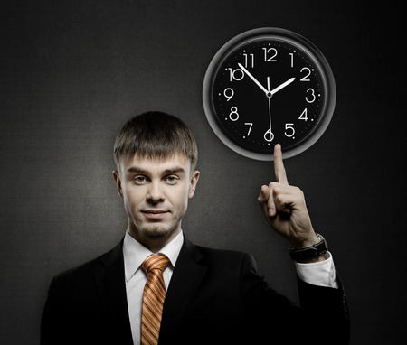 handsome businessman index finger point on clock, on dark grey background photo