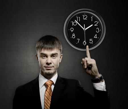 careerist: handsome businessman index finger point on clock, on dark grey background