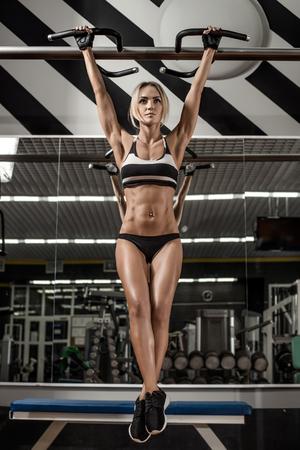 muskeltraining: Fitness junge Frau, die Übung auf horizontaler Balken im Fitness-Studio ausführen, vertikale Foto
