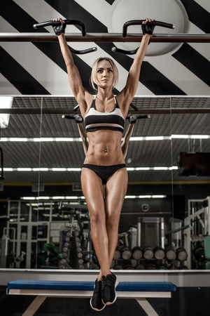 young fitness woman, execute exercise on horizontal bar in gym, vertical photo