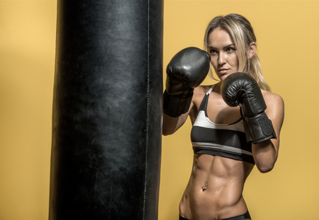 musculation: young boxer woman in boxing gloves with punching bag , on black and yellow background, horizontal photo Stock Photo