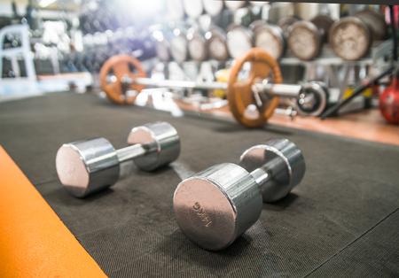 dumb bells: dumb bells in gym room, close up horizontal photo