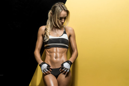 musculation: young fitness woman on black and yellow background, horizontal photo