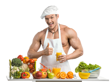 Man bodybuilder in white toque blanche and cook protective apron, concoction freshly squeezed orange juice  , on whie background, isolated Stock Photo
