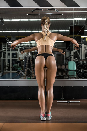 musculation: young fitness woman with beauty buttocks, execute exercise with exercise-machine Cable Crossover in gym, vertical photo