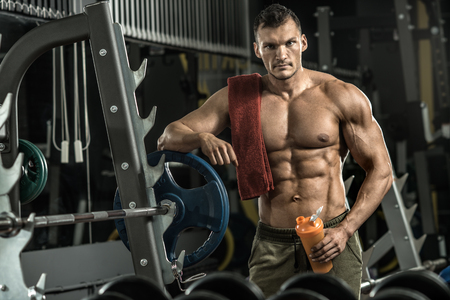 food supply: guy bodybuilder tired in gym hold shaker with sportive nutrition - protein of shaker , vertical photo