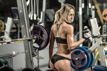 young fitness woman tired in gym hold shaker with sportive nutrition - protein of shaker , horizontal photo