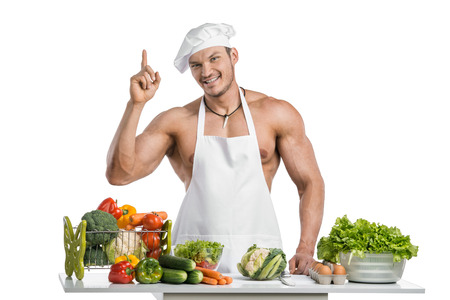 toque blanche: Man bodybuilder in white toque blanche and cook protective apron, concoction vegetables and fruit , on whie background, isolated