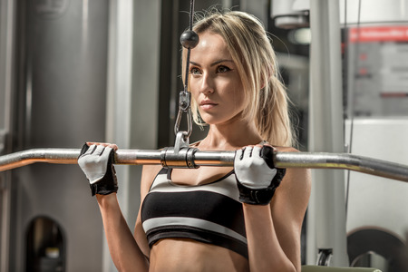 tough girl: young fitness woman execute exercise with exercise-machine in gym, horizontal photo Stock Photo