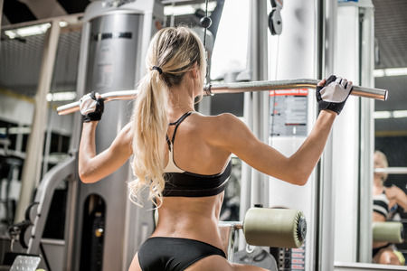 young fitness woman execute exercise with exercise-machine in gym, horizontal photo Stock Photo