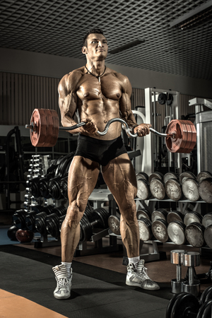 musculation: bodybuilder guy , execute exercise with weight in gym Stock Photo