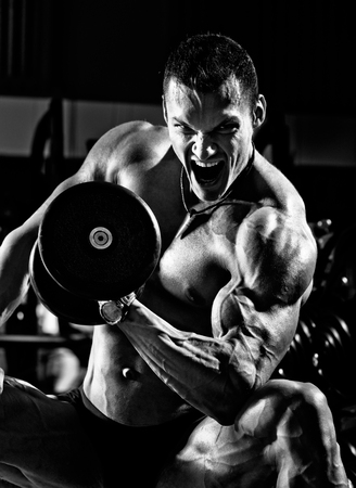 execute: bodybuilder man, execute exercise with  dumbbells, on black background, black-and-white photo