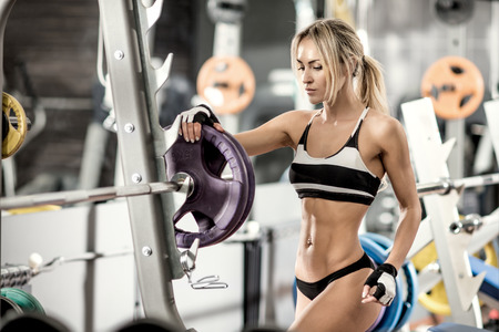 musculation: young fitness woman in gym, horizontal photo