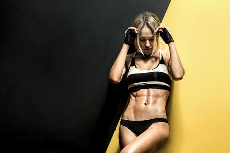 sportsman: fitness mujer joven en traje de baño en el fondo negro y amarillo, foto horizontal Foto de archivo