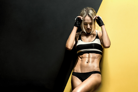 musculation: young fitness woman in swimsuit on black and yellow background, horizontal photo