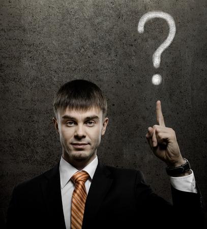 likeness: handsome businessman index finger point upwards on question, on dark grey background