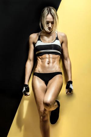 muskeltraining: Fitness junge Frau im Badeanzug auf schwarzen und gelben Hintergrund, vertikale Foto
