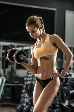 slim women: young fitness woman execute exercise with dumbbells in gym, vertical photo
