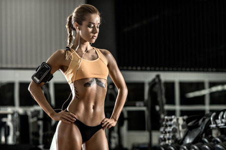 musculation: young fitness woman tired in gym and listen music with headset, horizontal photo Stock Photo
