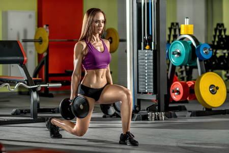 execute: beautiful girl, execute exercise with dumbbells, in dark gym