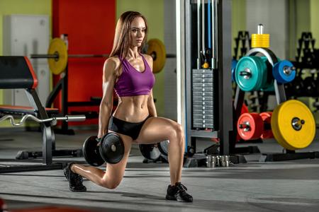 en cuclillas: hermosa niña, ejecutar el ejercicio con pesas, en el gimnasio oscura