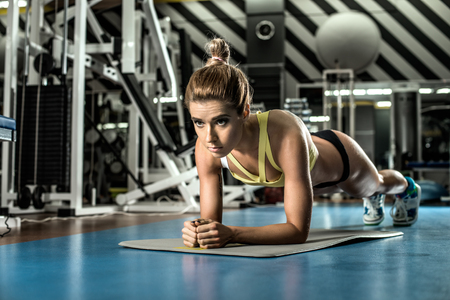 execute: young fitness woman execute exercise plank in gym, horizontal photo