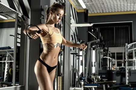 musculation: young fitness woman execute exercise with exercise-machine Cable Crossover in gym, horizontal photo