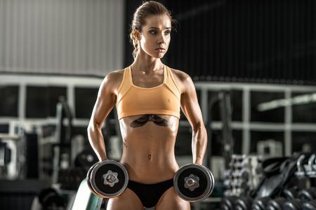 muskeltraining: junge Frau Fitness ausführen Übung mit Hanteln im Fitness-Studio, horizontale Foto