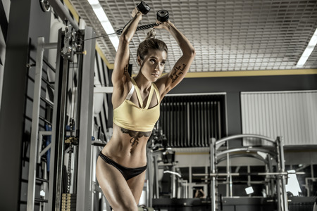 brawny: young fitness woman execute exercise with exercise-machine Cable Crossover in gym, horizontal photo. FOCUS ON STOMACH! Stock Photo