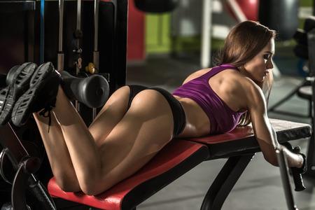 jonge fitness vrouw uit te voeren oefening met de uitoefening-machine op de benen en de gluteus, buig de benen, in de sportschool, horizontale foto Stockfoto
