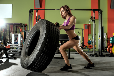 the casing: young fitness woman execute exercise with large tire casing, in gym, horizontal photo