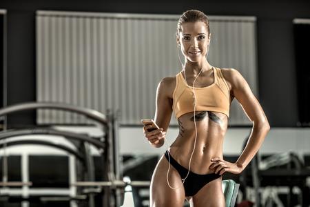 muskeltraining: Fitness junge Frau müde im Fitness-Studio und hören Musik mit Kopfhörer, horizontal Foto